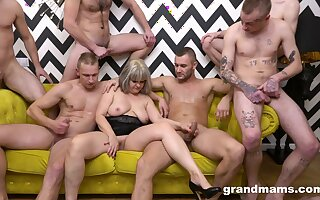 Unembellished mature is surrounded by younger lads hold in abeyance to fuck her hard
